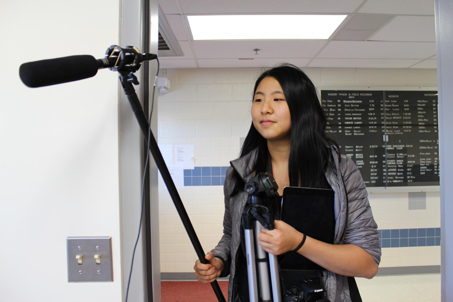 Carrying a <em>tjTV</em> tripod and microphone, Virginia Student Journalist of the Year Christine Zhao walks into the security room at Thomas Jefferson High School. Zhao was was preparing to interview security employee Charles Phillips for an online series on the stories of African-American students and staff.
