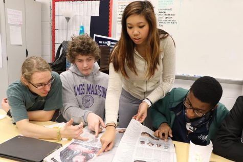 Pointing out design elements, Nyah Phengsitthy, an editor-in-chief at the <em>Newsstreak</em>, works with freshman staff members.