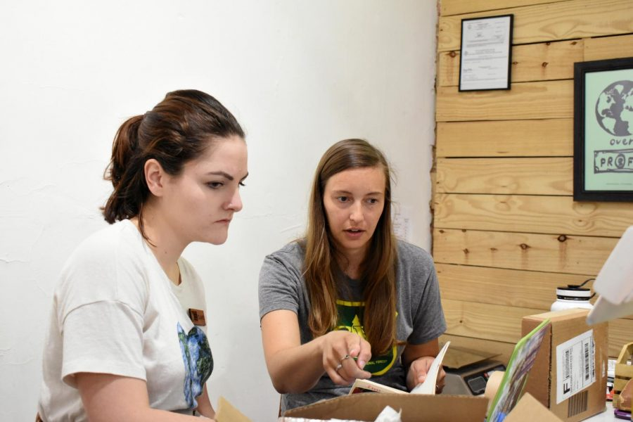 Allie Emerick (right) speaks with her employee about fulfilling orders.