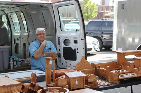 Satisfied with his work, woodworker Jim Dellinger displays the fruit of his hobby at Harrisonburg's Farmer's Market.