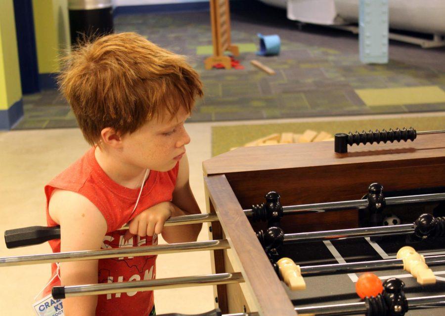 kid playing foosball