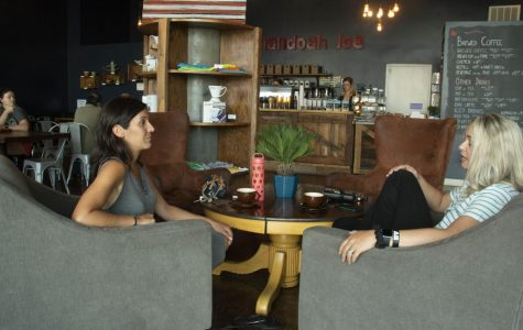Two customers chat over coffee in the seating area of Shenandoah Joe.